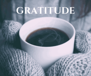 hands in mittens holding warm hot cup of coffee with gratitude written in bold