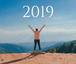 expat woman reaching her 2019 goals at top of mountain with arms outstretched