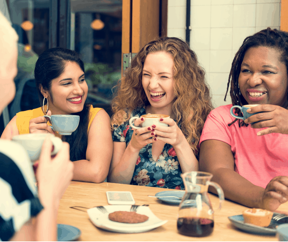 Diverse, international women friends drinking coffee together and laughing.