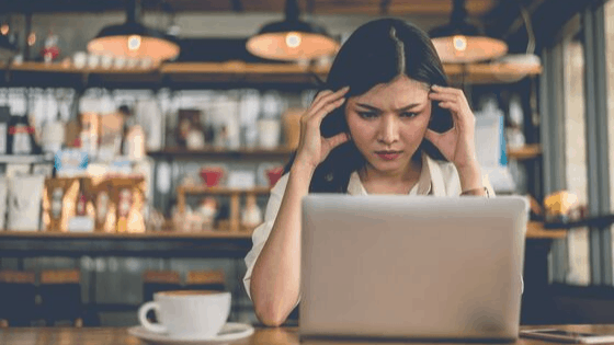 expat woman in coffee shop looking stressed about chaos